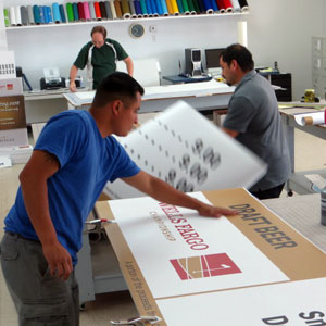 People Working In Sign Shop